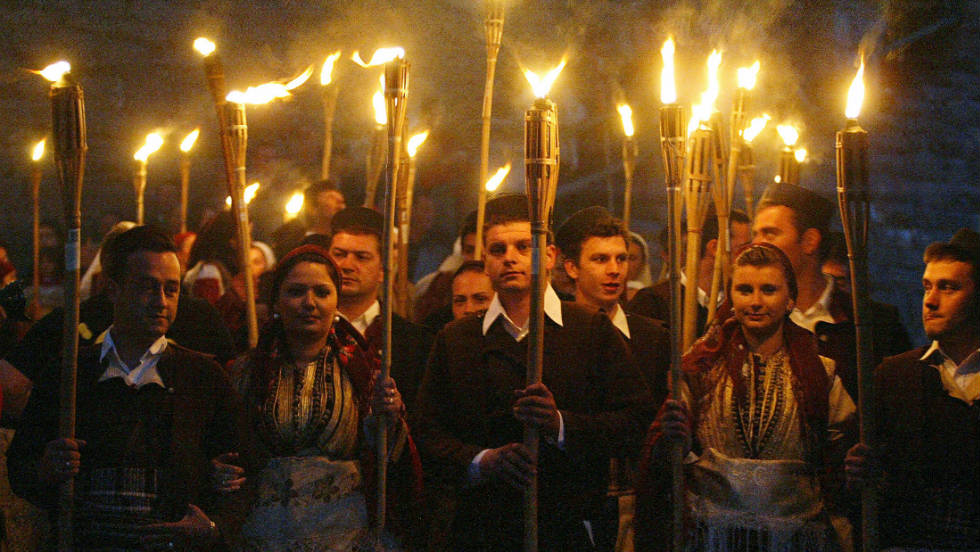 Orthodox christian men and women hold torches as they participate in a traditional Macedonian wedding procession.