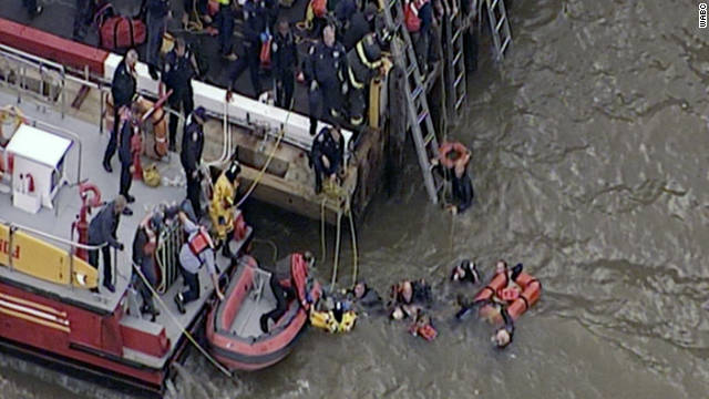 Rescuers pull people out of the East River after a helicopter crashed into the New York waterway.