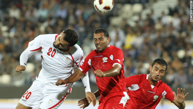 Iran's Mohammad Ghazi, left, leaps with Palestine midfielder Mali Kaware at Azadi Stadium on Wednesday.