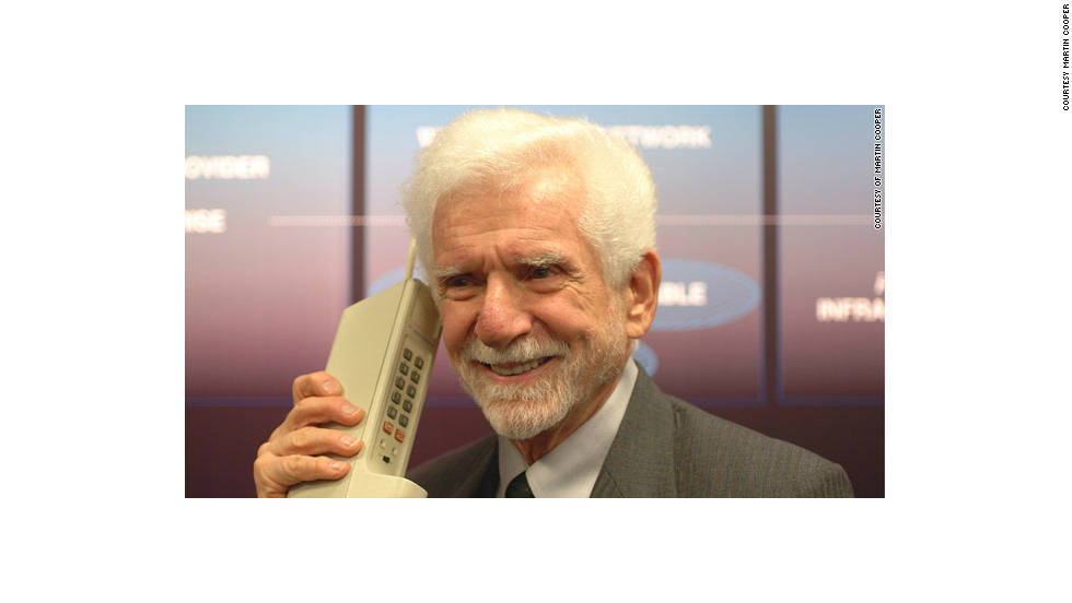 Martin Cooper hoists an early phone, the Motorola DynaTAC 8000X. Cooper made what is widely considered to be the first cellphone call from a New York City sidewalk in 1973.