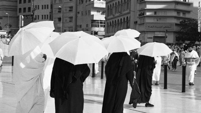 A Reem Al Faisal shot of people using umbrellas to protect them from the sun