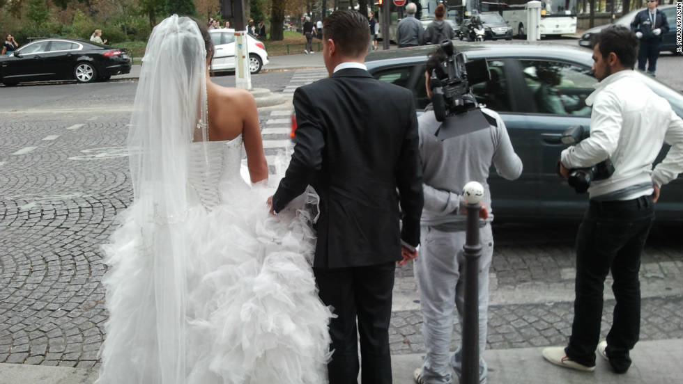 No limo needed: Newlyweds negotiate a Paris intersection after posing for photos on the Pont Alexandre III.