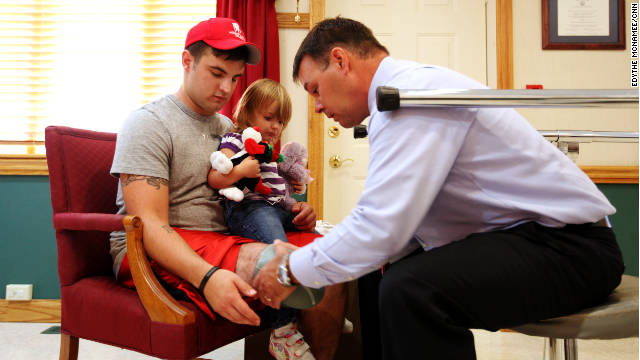 Roger Howard helps Matthew Hayes, with his daughter, get fitted for a new prosthetic leg.