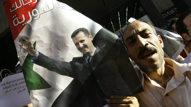 Syrians demonstrate in support of President Bashar al-Assad (poster) in central Damascus on August 23, 2011.