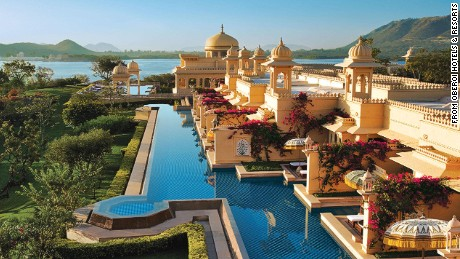 The Oberoi Udaivilas at Udaipur is built in the style of a traditional Indian palace, with gold-leaf domes and sand-colored walls reflected in the waters of Lake Pichola and the hotel's pools.