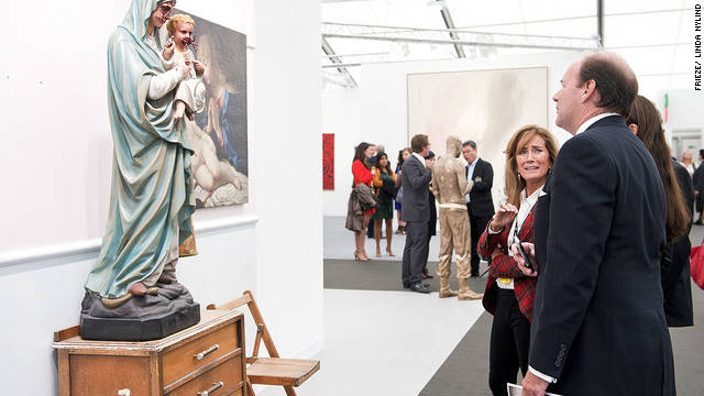 Visitors stop in front of a work by Jake and Dinos Chapman at White Cube gallery's stand at the Frieze art fair, London.