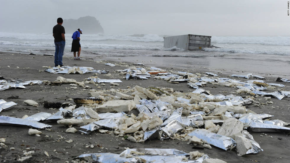 Local residents come to look at a washed-up container and litter on the beach on October 13.