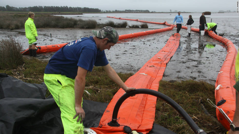 Workers construct oil booms at Maketu Estuary in the North Island's Bay of Plenty on October 13.
