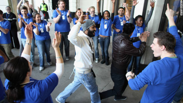Apple employees applaud a customer Friday morning as he enters the Covent Garden store in London to buy an iPhone 4S.
