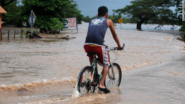 A man rides his bike on a flooded street in El Manglar, Honduras, on Sunday. Heavy rains continue to pummel Central America.