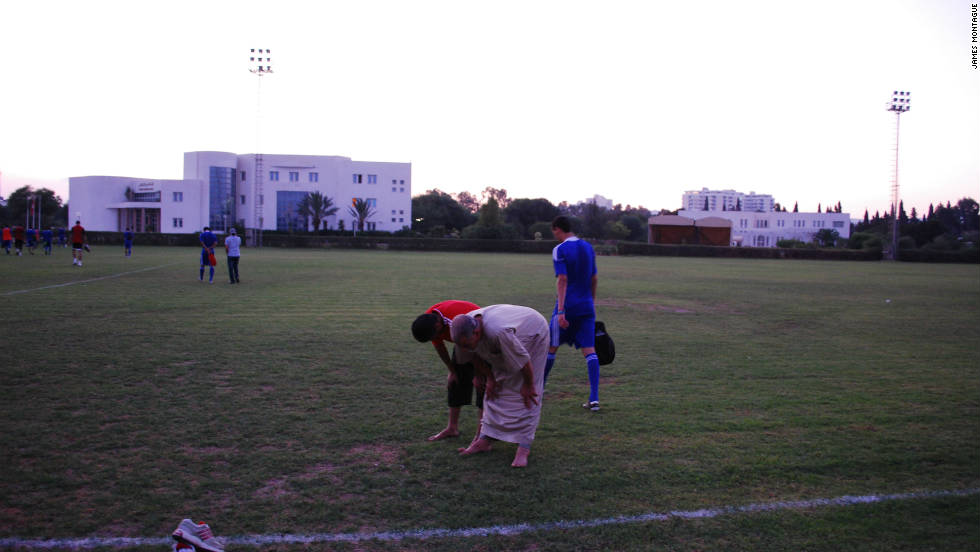 Members of the Libyan team's backroom staff pray after training.