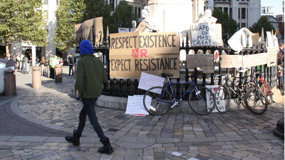 A demonstrator walks past signs at the protest camp outside St Paul's Cathedral in London.