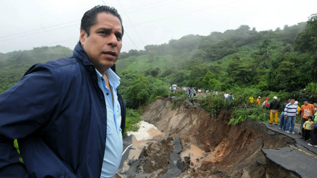 Honduran official Miguel Rodrigo Pastor checks landslide damage on the Pan-American highway near La Moramulca.