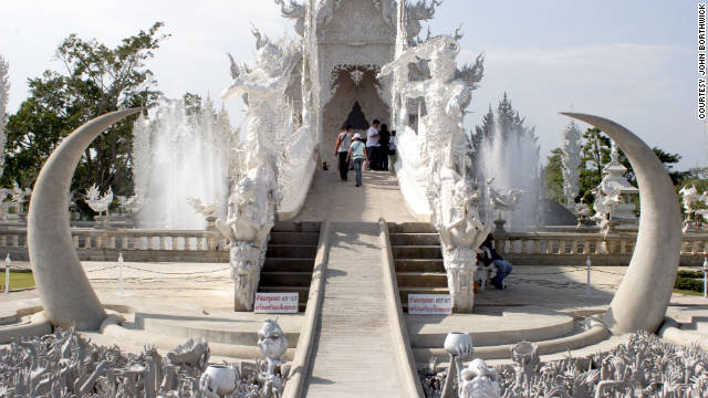 Visitors must cross a bridge to the Wat Rong Khun temple over a field of fangs and statues reaching up from hell.