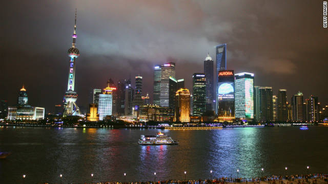 A sightseeing ship on the Huangpu River against the night skyline of Shanghai, China.