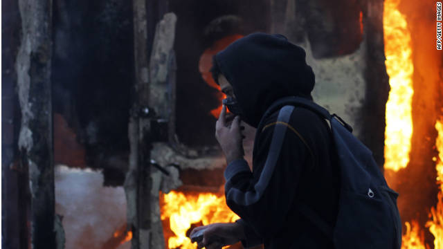 A protester covers his face and holds a stone as he walks in front of a burning in Athens .