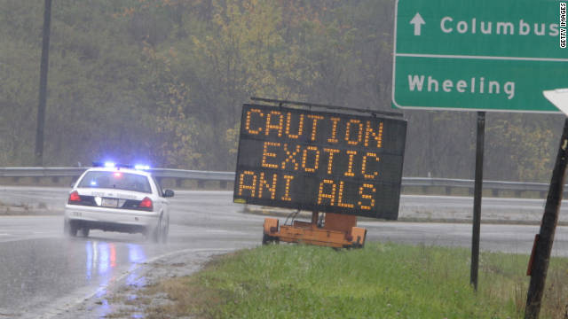 A police officer drives past a sign warning of wild animals on the loose on October 19  in Zanesville, Ohio.
