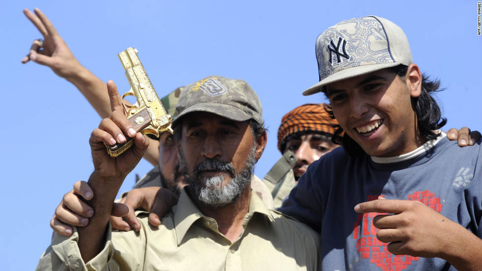 NTC fighters hold what they say is the ousted Libyan leader's gold-plated gun Thursday.