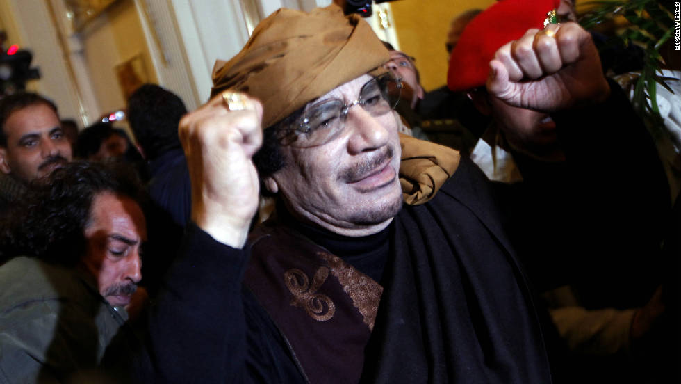 Gadhafi smiles and raises his arms as he enters the Rixos Hotel in Tripoli on March 8, 2011. A few months later, on October 20, Gadhafi will die of a gunshot wound to the head in his hometown of Sirte, Libya.