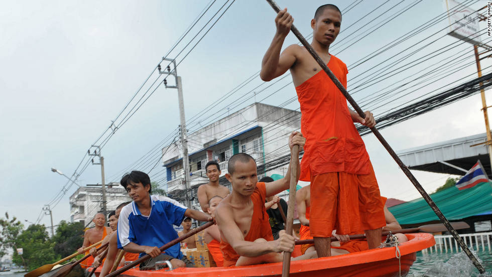 Thai Buddhist monks row a boat through floodwaters in the inundated Ban Bua Thong district of Nonthaburi province, suburban Bangkok on October 20.