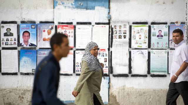 Tunisian people walk past a wall covered with posters of political candidates in Tunis two days before a historic election.