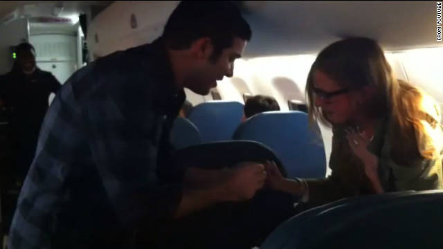 Arvin Shandiz presents Alexandra Williams with a ring on board a flight from Chicago to New York on Friday.