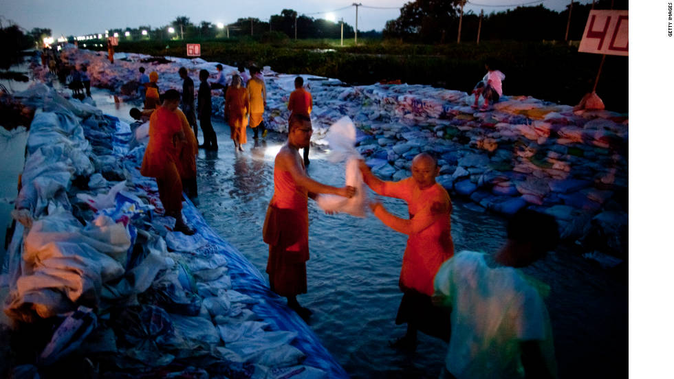 Dhammakaya monks and volunteers work to fortify the flood gate at Klong Rapi Pat Sunday on the outskirts of Bangkok, Thailand.