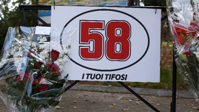 Flowers are laid under a sign displaying Simoncelli's racing number of 58 in his hometown of Cattolica.