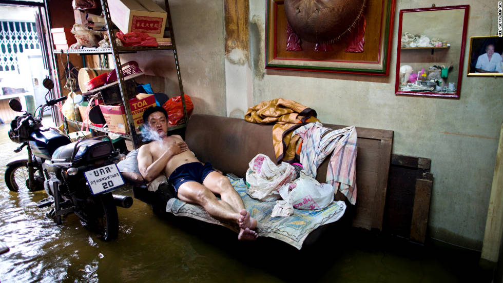 A man lies on a couch Wednesday in his flooded Bangkok home. Gov. Sukhumbhand Paripatra says that despite the risk, it is difficult to persuade people to leave their homes.