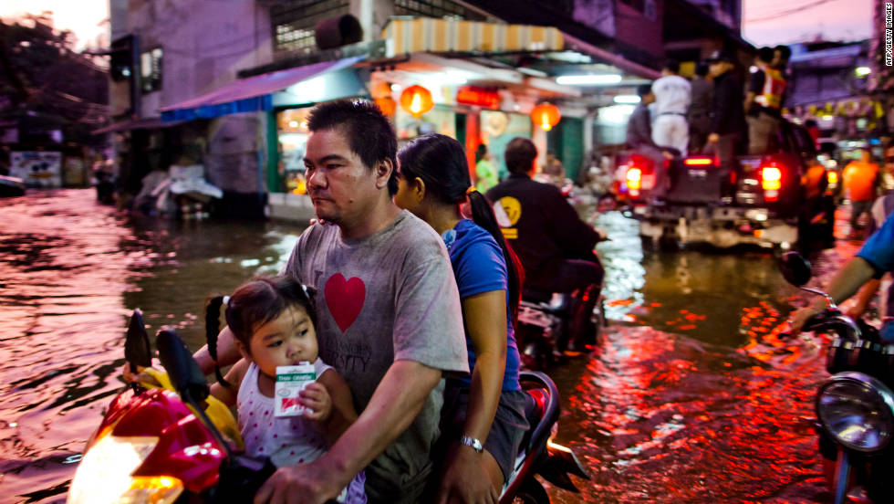 Chinatown residents make their way through a flooded street on Wednesday. The water has caused problems for small vehicles and led to traffic congestion.