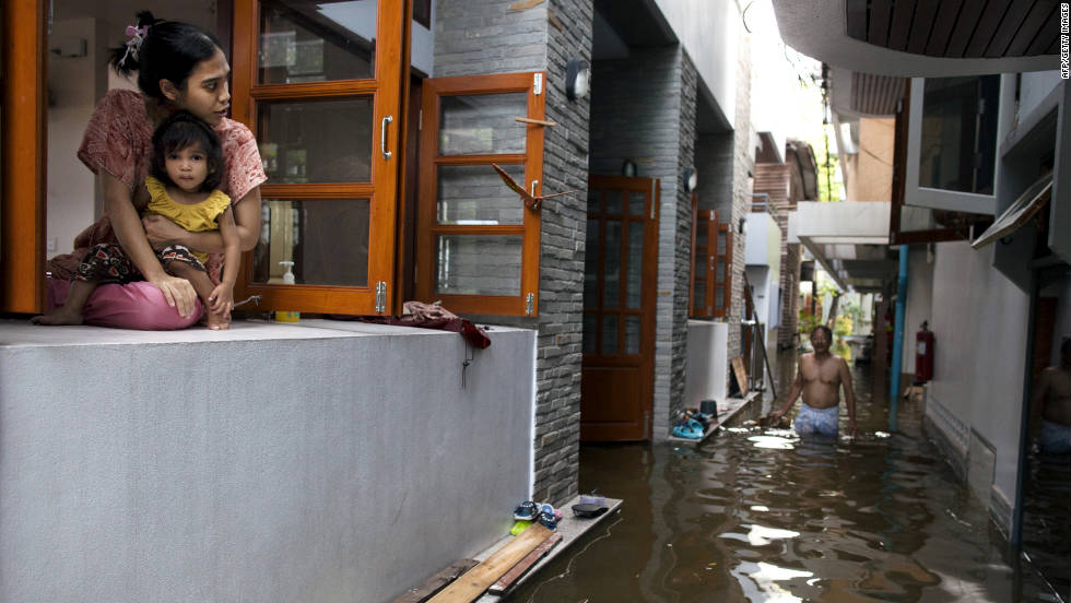 A woman sits with her daughter in the window of their flooded condo. Residents have been urged to flee the rising waters.