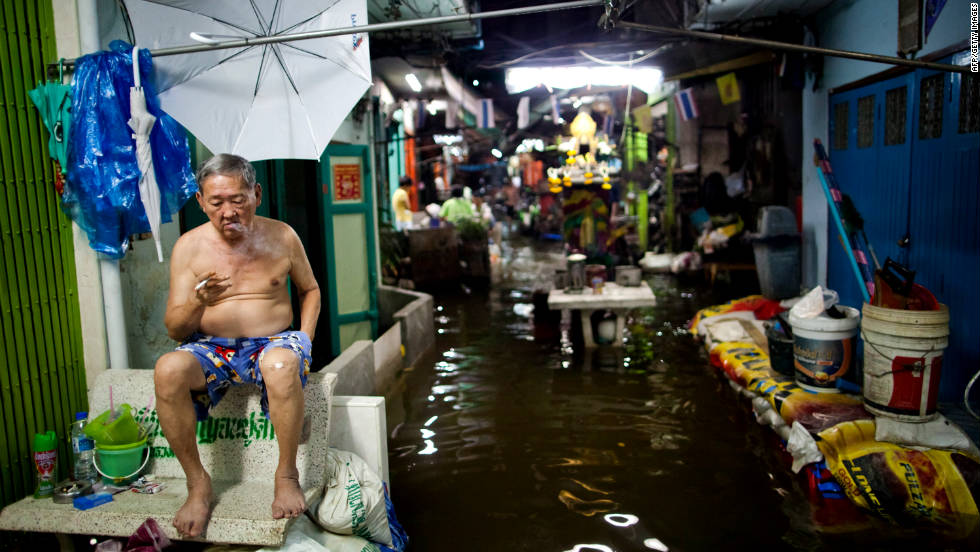 A man smokes a cigarette outside his home as floodwaters rise in Bangkok on Wednesday, October 26. The government has called the flooding the worst to afflict the nation in half a century.