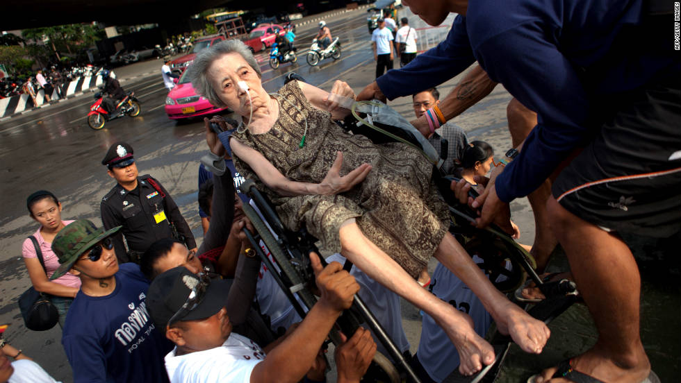 An elderly woman in Bangkok is helped onto a truck to be taken to a hospital. The flooding has affected more than 9.5 million people, authorities said.