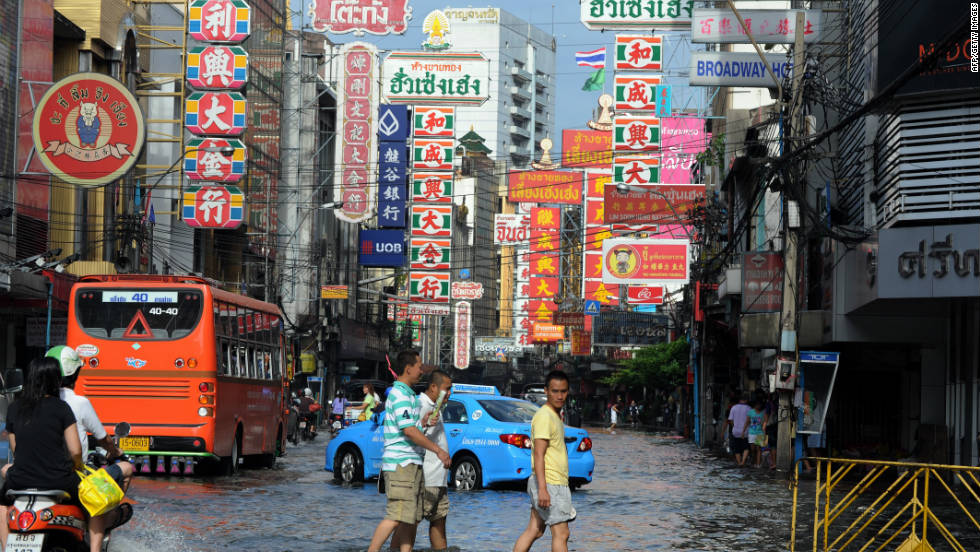 Thai residents walk in floodwaters along a street in the Chinatown section of Bangkok.