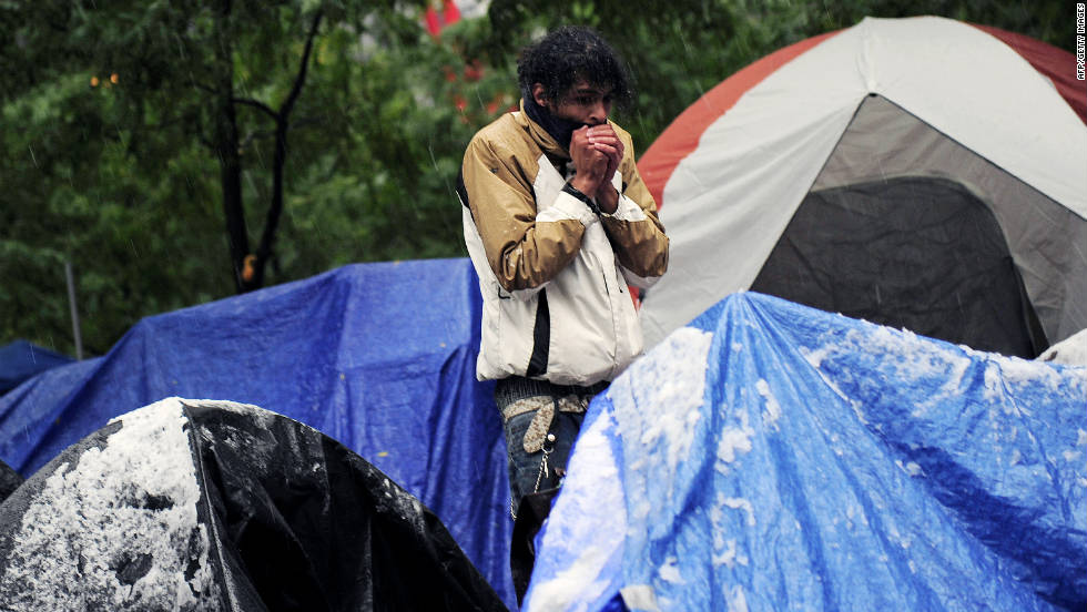 Snow covers tents as an Occupy Wall Street participant tries to warm up in New York on Saturday.