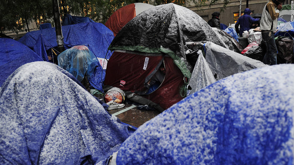 An Occupy Wall Street participant peeks out of his tent as snow blows through New York.