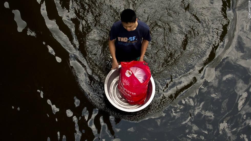 A Bangkok resident makes his way through a flooded street on Sunday.