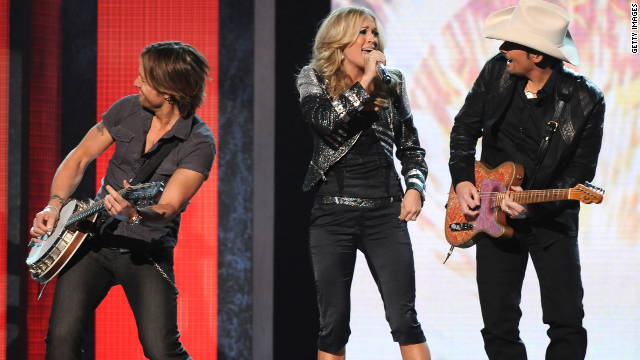 From left, Keith Urban, Carrie Underwood and Brad Paisley perform onstage during the 2010 CMA Awards in Nashville.