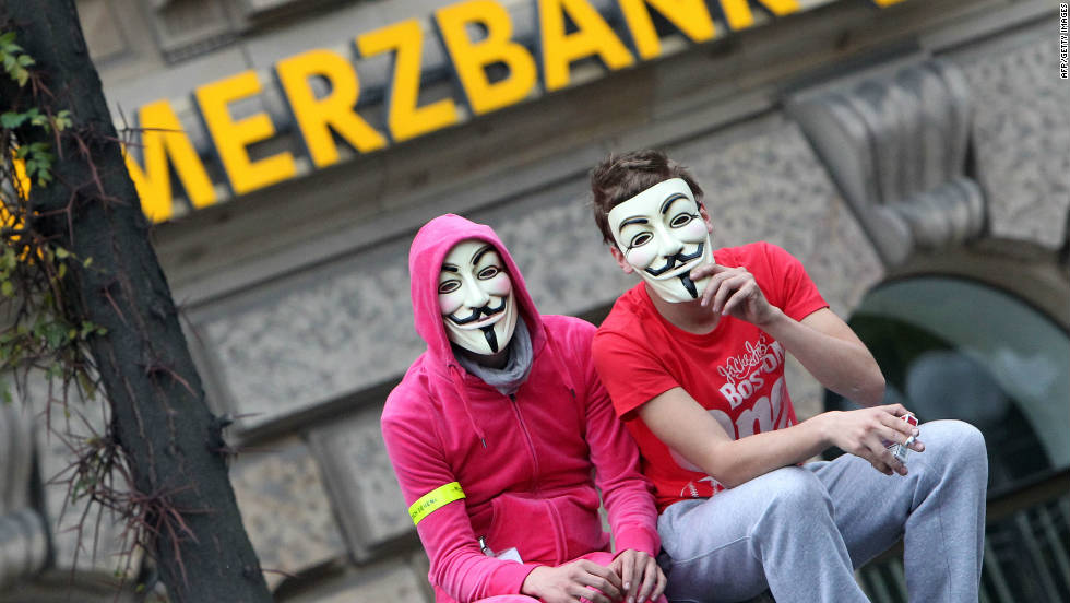 "Demonstrators wearing ""Vendetta"" masks sit in front of a Commerzbank branch in Frankfurt on October 29."