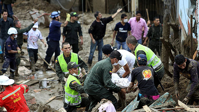 Residents, police officers and rescue workers retrieve the body of a victim in Manizales, Colombia, on Saturday.