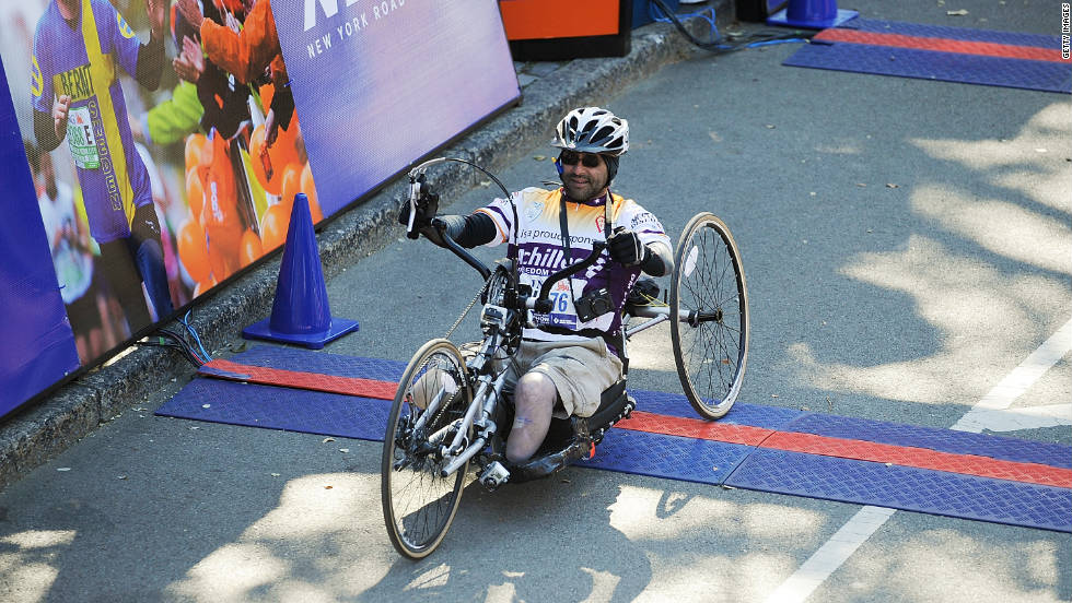 New York Times photographer Joao Silva finishes the marathon on Sunday. Silva lost both his legs last year covering the war in Afghanistan.