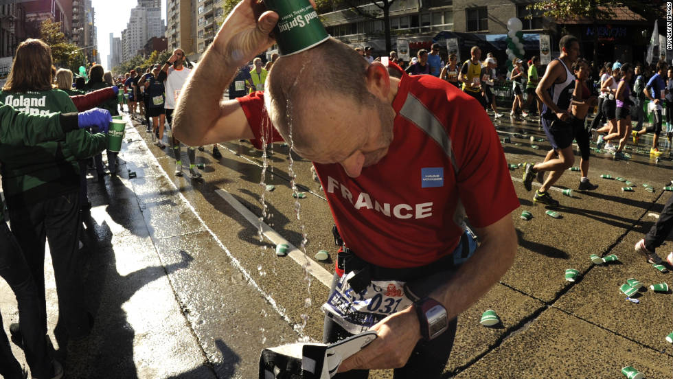 A participant cools off as volunteers hand out water to racers as they pass by.