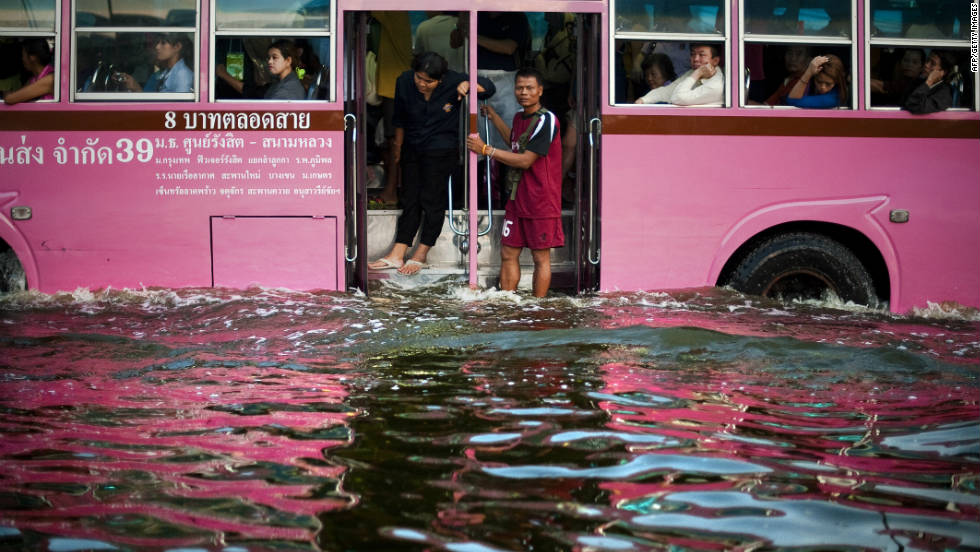 People stand on a bus as it makes its way through floodwater in the Lat Phrao district of Bangkok, November 7.