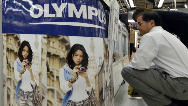 A customer checks a camera of Japanese optical giant Olympus at a Tokyo camera shop on October 27, 2011.