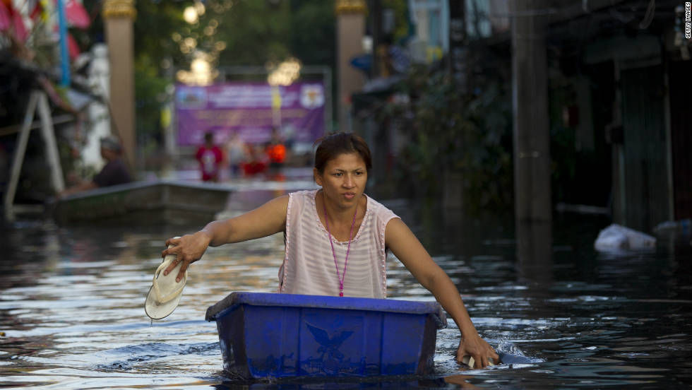 A Bangkok resident uses her footwear as paddles as floodwater moves towards central Bangkok, November 7.