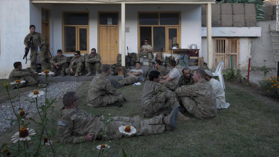 Meanwhile, the U.S. forces relax on the grass of the district compound after the shura. Lt. Col. Dan Wilson sits in a circle with the local Afghan Army colonel and a security adviser.