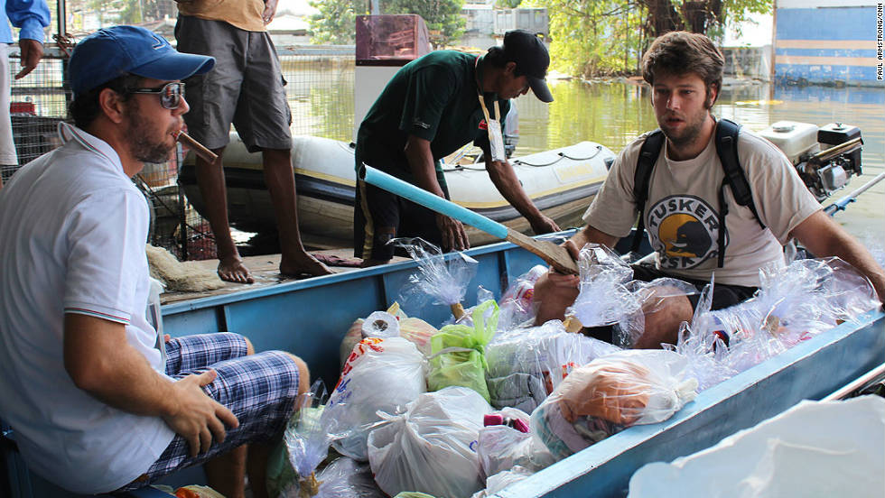 Romeo and Alex load up the boat and spend all day distributing supplies, from food and water to clothes and books, to those they come across.