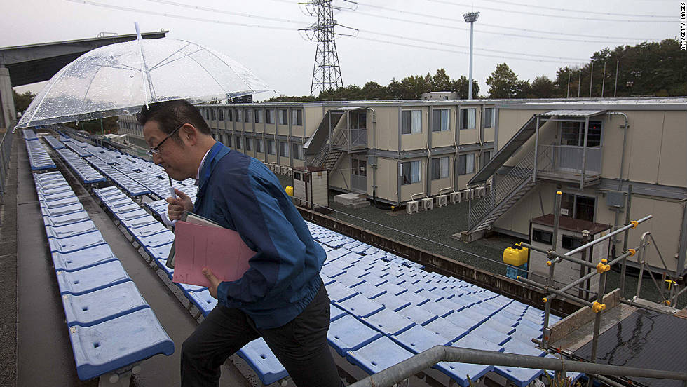 A employee of the Tokyo Electric Power Company walks up stairs near temporary housing built for workers who live at J-Village,  at the former soccer training complex.