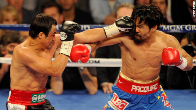 Juan Manuel Marquez (L) and Manny Pacquiao trade blows during their fight in Las Vegas.