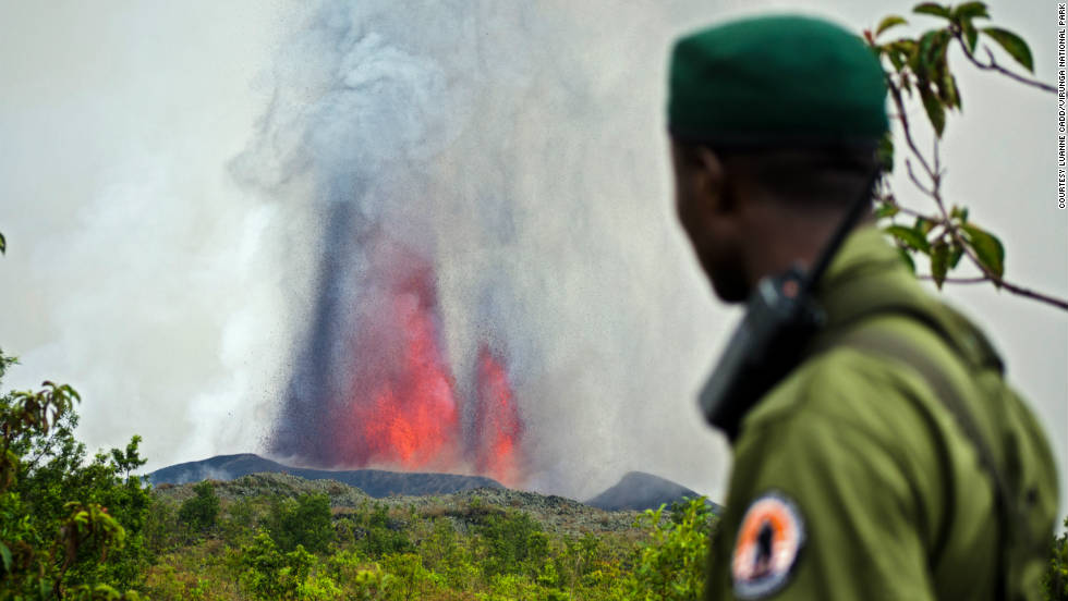 A park ranger looks on as Mount Nyamulagira erupts in front of him.